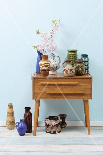 Retro ceramic vases on top of and beneath chest of drawers against wall painted pale blue