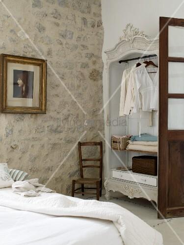 Rustikales Schlafzimmer mit offenem Kleiderschrank und ...