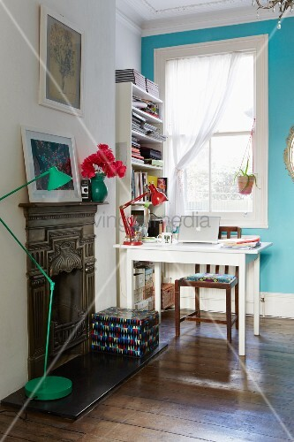 White table and wooden chair below lattice window in turquoise wall