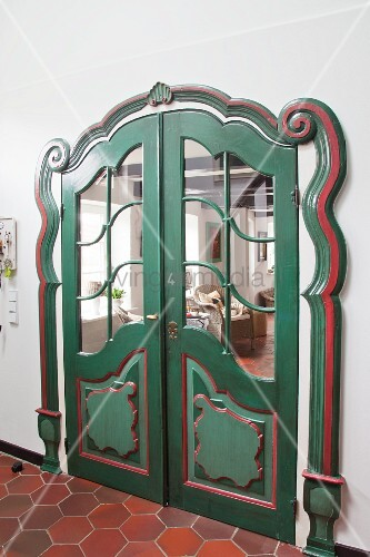 Artistically decorated double doors painted green and red in renovated farmhouse