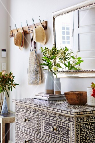 Kunstvolle Ethno-Kommode mit Einlegearbeiten in Diele und eleganter Wandspiegel neben rustikaler Garderobenhakenleiste