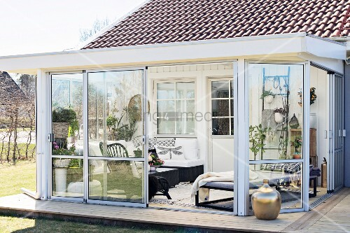 Comfortable furniture in conservatory extension and wooden, Scandinavian-style wooden deck