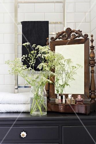 Antique vanity mirror, perfume bottles and glass vase of cow parsley on top of black bathroom cabinet