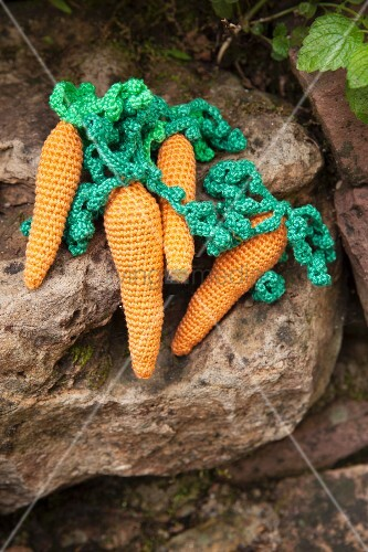 Hand-made crocheted carrots on stone in garden