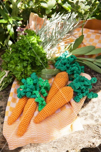 Hand-made crocheted carrots and fresh herby on tea towel
