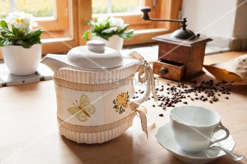 Hand-made, embroidered coffee-pot cosy in front of vintage coffee mill and coffee beans on wooden table