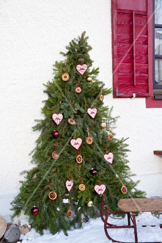 Fir branches arranged in Christmas-tree shape on house façade decorated with home-made baubles
