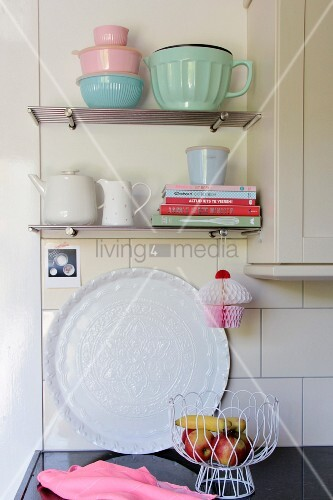 Stacked books and retro crockery on wall-mounted kitchen shelves