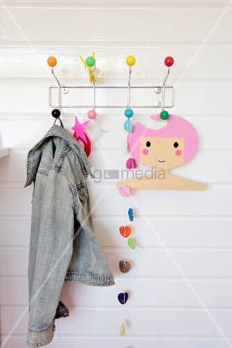 Colourful crocheted garland, denim jacket and coathanger with cartoon girl motif hung from coat rack