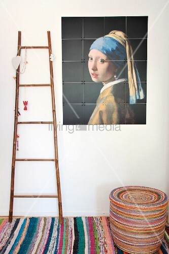 Reproduction of 'Girl with a Pearl Earring' next to decorations on ladder on rag rug