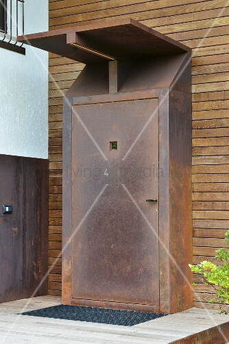 Rusted front door and porch on wood-clad façade