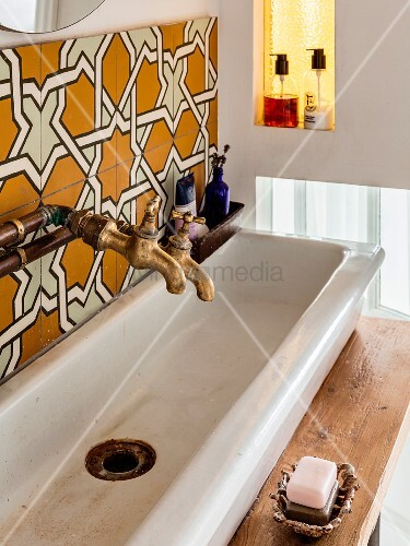 Vintage-style washstand with old-fashioned tape, ornate tiles and stained glass in niche to one side