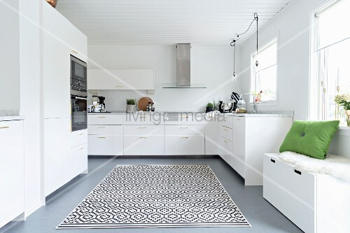 Storage bench below window and rug with graphical pattern in elegant white fitted kitchen