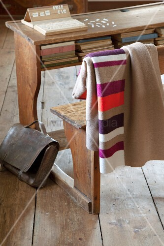 Striped and plain blankets made from warm, boiled wool hung over backrest of vintage school bench