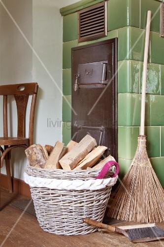 Firewood basket with hand-sewn handle on woven felt border next to tiled stove