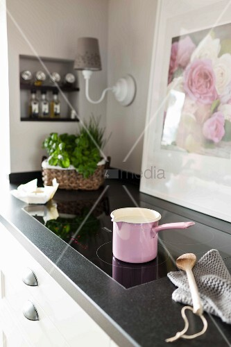 A pink milk pan on an induction stove