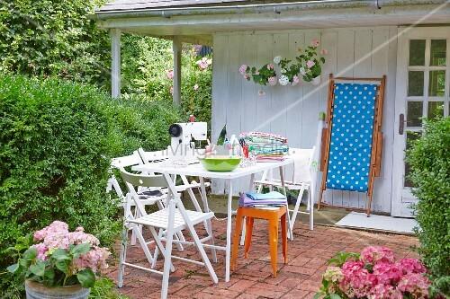 n hmaschine und n hutensilien auf tisch mit klappst hlen im sommerlichen garten bild kaufen. Black Bedroom Furniture Sets. Home Design Ideas
