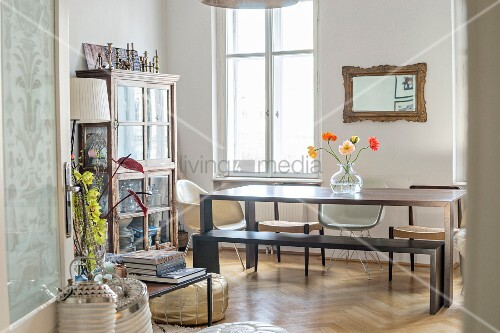 Display case, wooden table and various chairs in dining area of period apartment