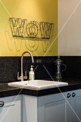 White sink in granite kitchen worksurface below decorative lettering on yellow wall