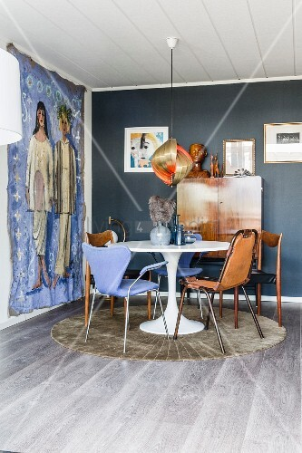Round table and various chairs in dining area with wall hanging
