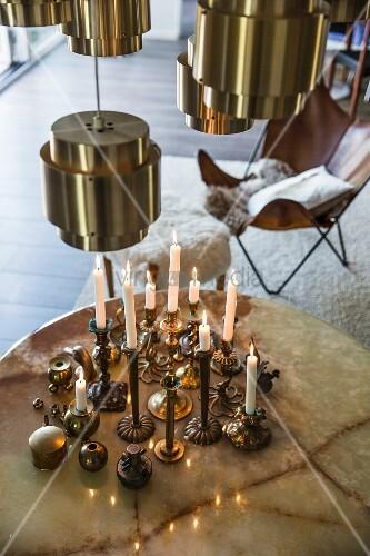 Brass candlesticks on round table below brass lampshades