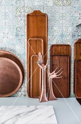 Various wooden trays and hand-shaped ornaments in front of blue patterned wall tiles