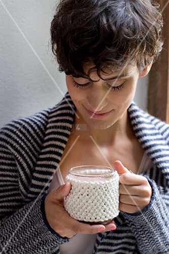 A hand-knitted cup sleeve made of cotton yarn