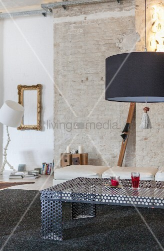 Perforated sheet metal coffee table in front of unrendered wall in loft apartment