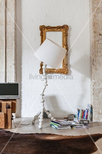White standard lamp in front of gilt frame on white-painted brick wall