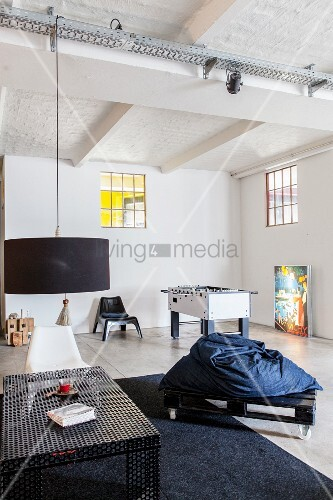 Lounge area and table football table in industrial-style loft apartment