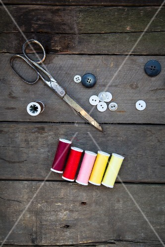 Scissors, buttons and cotton reels on wooden surface