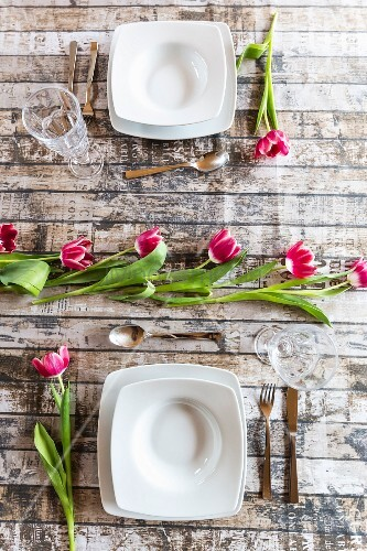 Two place settings on table decorated with tulips