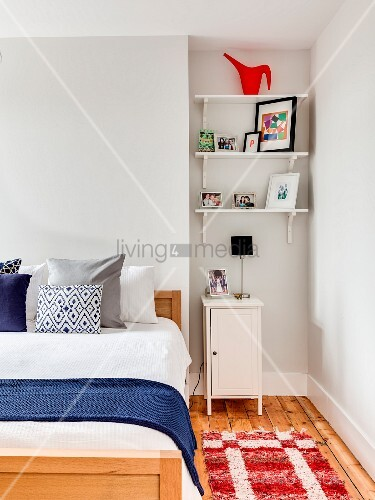 Shelves and bedside cabinet in niche next to bed