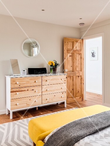 White chest of drawers with wooden drawer fronts in bedroom