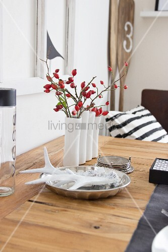 White vase of rose hips and antlers in silver dish decorating table