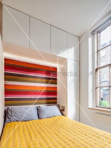 Kleines Schlafzimmer mit Einbauten und Streifenmuster am Betthaupt
