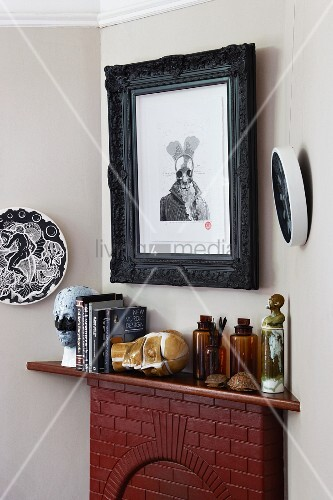 Modern graphical artwork in black frame above ornaments on mantelpiece