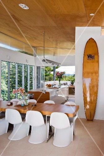 Offene Küche mit elegantem Essbereich, angelehntem Surfbrett und Fensterfront