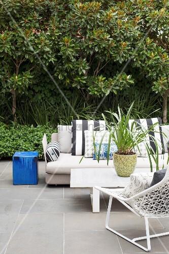 Gemütliche Outdoor-Lounge mit heller Couch auf Terrasse