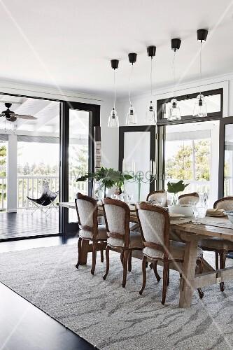 rustikaler holztisch mit gepolsterten st hlen und pendelleuchte in hellem essbereich bild. Black Bedroom Furniture Sets. Home Design Ideas