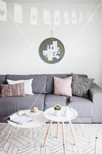 Graues Polstersofa und weisse Tabletttische in Wohnzimmer mit nordischem Flair