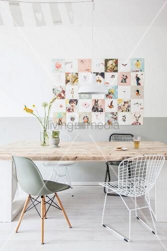 Esstisch mit rustikaler Holzplatte und verschiedene Klassikerstühle vor Retro Wandbild