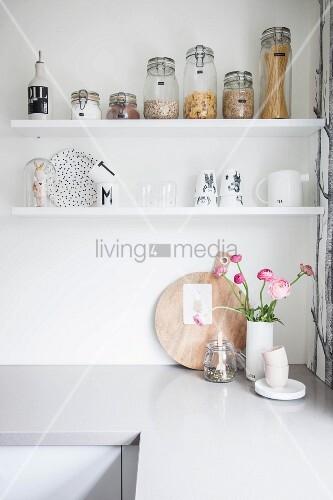 Weisse Regalbretter mit Vorratsgläsern und Geschirr über Küchenzeile