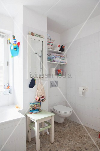 Pebble floor, toilet, wooden stool and mirror on wall in white bathroom