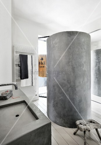 Concrete cylindrical shower in bathroom with concrete sink and vintage wooden stool