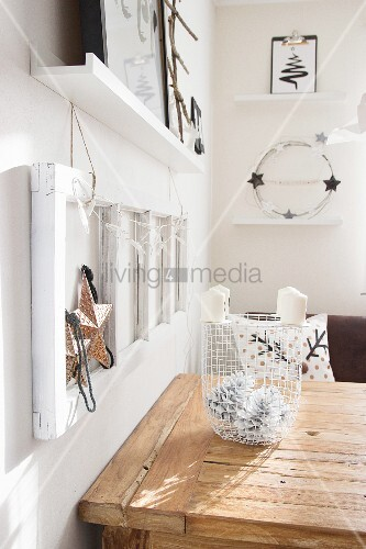 White metal basket of pine cones and candles on wooden table below Christmas decorations in frames on wall