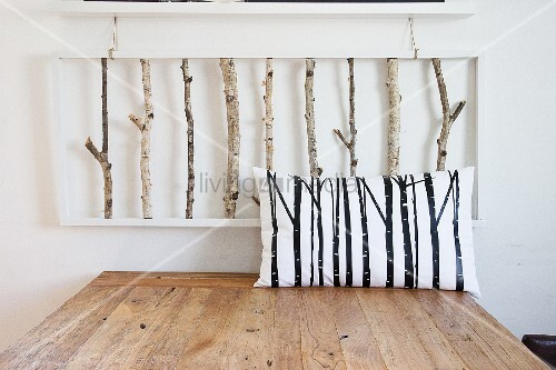Scatter cushion with pattern of branches on wooden table below 3D artwork made from birch branches