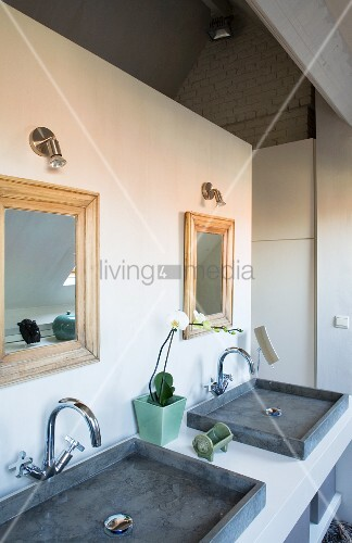Two grey countertop sinks on washstand below mirrors on partition wall in ensuite bathroom