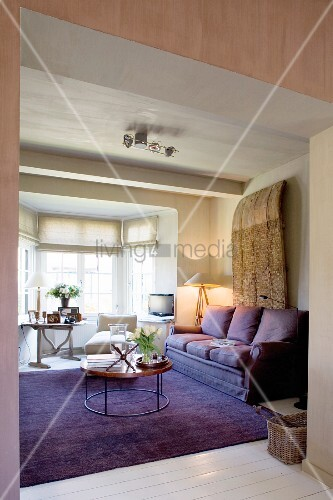 Purple couch and matching rug in comfortable lounge area in front of bright bay window