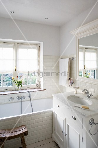 Bathtub and washstand with marble counter in bathroom